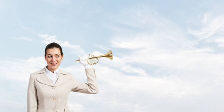 Beautiful woman holding trumpet brass near ear and listening. Young businesslady in white business suit and gloves posing with music instrument on blue sky background. Business concept with musician Stock Photo