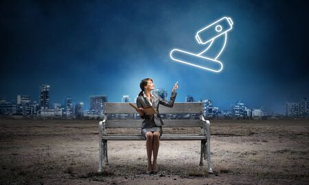 Young woman holding open book on wooden bench outdoor. Science research concept. Beautiful girl finger pointing at microscope symbol in night sky. Modern cityscape panorama at night.