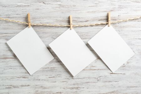Blank sheets of white paper hanging on twine rope with wooden clothespins. Elegant photo frames on painted background. Scrapbooking and handmade creativity. Wooden wall with copyspace for text