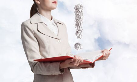 Attractive woman holding open notebook with exclamation mark. Business consultation and legal assistance. Elegant young woman in white business suit with open book in hands on background of blue sky. Stock fotó - 129875744