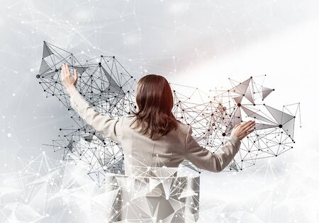 Businesswoman controlling and managing abstract network structure. Back view long haired woman in white suit sitting on white chair. Social connection and networking. Global cloud technology concept Foto de archivo - 129875750