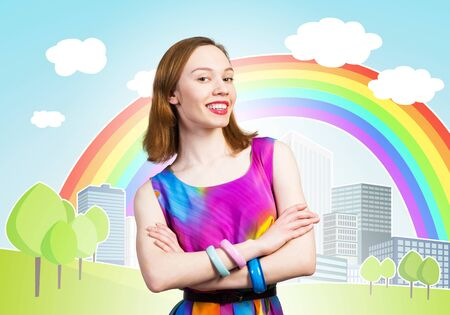 Joyful woman standing with folded arms. Elegant lady in colorful dress and bracelets. Good looking redhead girl with charming smile. Flirty woman posing on background cartoon city with rainbow 写真素材