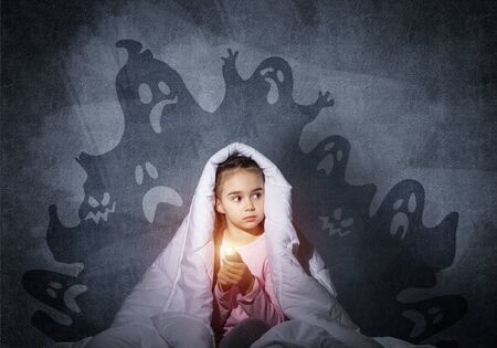 Scared girl with flashlight hiding under blanket. Frightened kid sitting in his bed at home. Night terrors of child. Beautiful girl in pajamas and boo ghosts silhouettes back on wall.