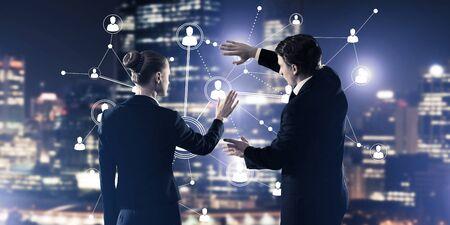 Uomo d'affari e donna di affari che stanno con il concetto posteriore e commovente del collegamento