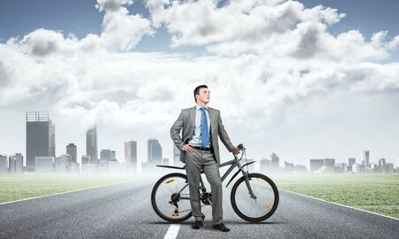 Successful man in business suit standing with bike. Businessman with bicycle on background of modern office buildings. Male cyclist posing on camera with bicycle. Man relaxing outdoors in sunny day.