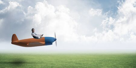 Happy aviator driving small propeller plane on background of natural landscape. Man in airplane flying low above green meadow. Nature panorama with green grass and cloudy sky in summer day.