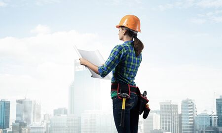 Female engineer in hardhat standing with technical blueprint. Side view of woman architect in checkered blue shirt inspecting construction on background of cityscape. Building project management