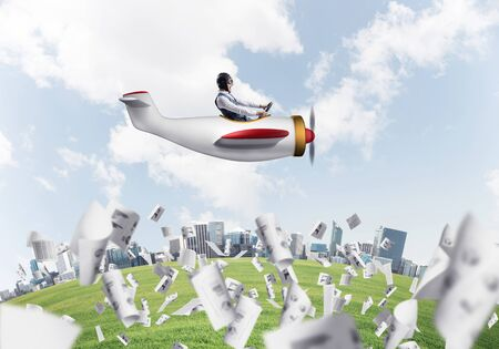 Businessman in leather helmet and goggles flying in propeller plane. Aviator driving small airplane above falling paper sheets with business infographics. Rounded city skyline with high skyscrapers