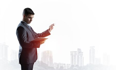 Handsome businessman standing and finger pointing at something. Side view of man in business suit and tie on background foggy cityscape. Financial specialist with raised hand promotion mockup. 写真素材
