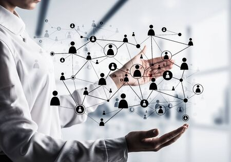 Business woman in shirt keeping black social media network structure in hands with office view on background. Mixed media. Stock Photo