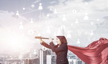Young confident businesswoman wearing red cape against modern city background and looking in spyglass Stock Photo