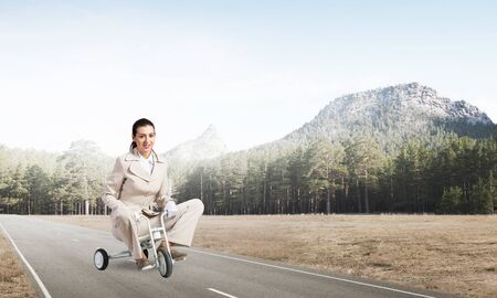 Beautiful happy woman riding childrens bicycle on asphalt road. Young employee in white business suit cycling small bike outdoor. Nature landscape with green grass. Professional career start concept