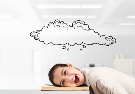 Bored business woman lying on desk with open book. Speech bubble in shape of cloud above head. Tired lady yawning in light office interior. Paperwork deadline and overwork in office concept. Stockfoto