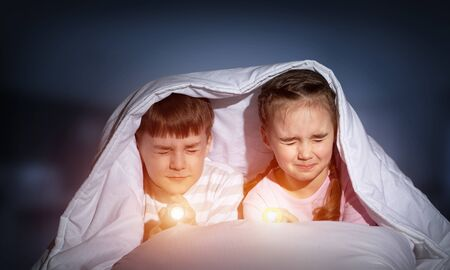 Children with flashlight lying in bed. Little girl and boy with closed eyes hiding under blanket together. Covered kids afraid of dark at night on background of deep blue sky. Night terrors of child