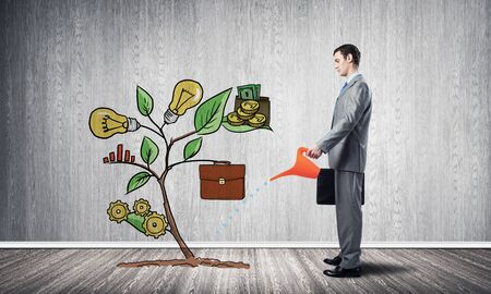 Businessman watering drawing tree with can. Green plant consisted of business infographic signs. New startup development. Business support and assistance metaphor. Investing into ideas.