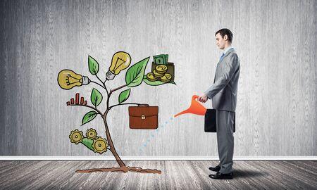 Homme d'affaires arrosant l'arbre de dessin avec la boîte. La plante verte se composait de signes infographiques commerciaux. Développement de nouvelles startups. Métaphore de soutien et d'assistance aux entreprises. Investir dans les idées.