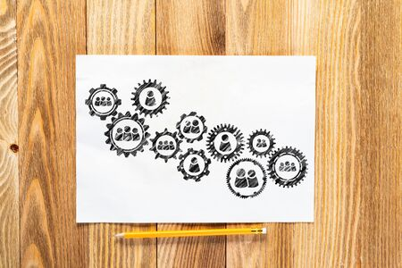 Human resource recruitment pencil hand drawn with group of rotating cogwheels. Headhunting and team building sketch on wooden surface. Top view of workplace with paper and pencil lying on wooden desk.