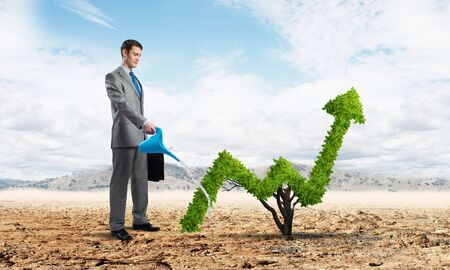 Businessman watering green plant in shape of of grow up trend in desert. Business analytics and statistics. Friendly ecosystem for business and investment. Business growth and development. Stock fotó