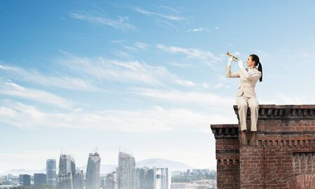 Young woman playing trumpet and sitting on roof. Girl in white business suit with music brass instrument posing high above modern city. Imagination and inspiration. Mixed media business concept.