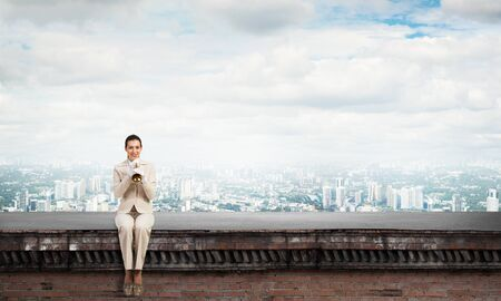 Attractive young woman playing music on roof of building. Brave businesswoman in white business suit with trumpet instrument sitting on edge of roof. Music performance on roof in modern city. Stock fotó