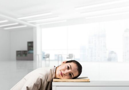 Bored business woman lying on desk with open book. Young tired student trainee in white business suit relaxing in light office interior. Paperwork deadline and overwork in office concept.
