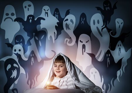 Smiling boy with flashlight hiding under blanket. Happy kid lying in his bed at home. Portrait of cheerful boy in pajamas and funny boo ghosts back on night sky. Mysterious phantoms in darkness