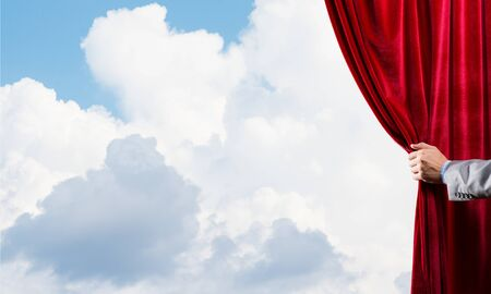 Human hand opens red velvet curtain on blue sky background Reklamní fotografie