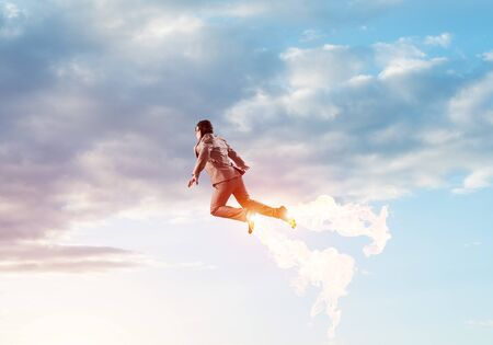 Businessman in aviator hat flying in cloudy blue sky as superhero. Business person as superhero with jet flame flying planet atmosphere. Goal achievement concept. Career ambition and growth.