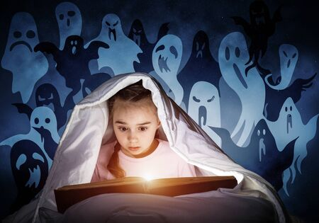 Engrossed little girl reading book in bed after bedtime. Kid in pajamas with flashlight hiding under blanket. Fearful girl and imaginary monsters on deep blue background. Child reading fairy tales. Stock fotó