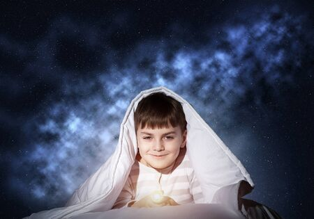 Happy child with flashlight hiding under blanket. Smiling kid lying in bed at home. Funny game at bedtime. Young boy can not sleep at night. Cheerful boy in pajamas on background of deep starry sky