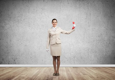 Woman keep at distance vintage red phone. Call center operator in white business suit posing with landline phone in room. Hotline telemarketing and communication. Business assistance and support