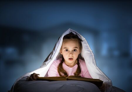 Little girl reading magic stories in bed before going to sleep. Pretty child hiding under blanket. Covered kid can not sleep at night. Portrait of beautiful girl in pajamas on blue blurred background