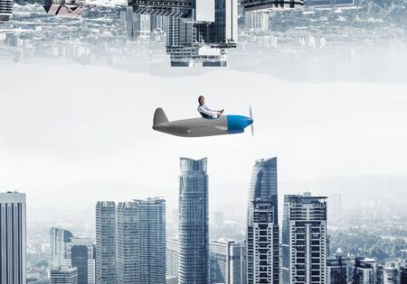 Young pilot sitting in cabin of small airplane. Abstract image of two modern urban worlds located upside down to each other. Funny man in aviator hat and goggles driving propeller plane.