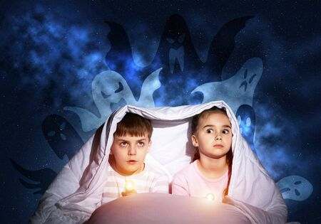 Scared girl and boy with flashlights hiding under blanket from imaginary phantoms. Frightened kids sitting in bed on night sky background. Children in pajamas and boo ghosts silhouettes above them