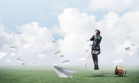 Young woman sitting on big light bulb. Girl in business suit keeps hands on face for surprise. Businesswoman playing hide and seek on green meadow with flying paper planes. Hide from problems.