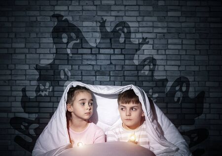 Scared girl and boy with flashlights hiding under blanket from imaginary phantoms. Frightened kids sitting in bed on background grey wall. Children in pajamas and boo ghosts silhouettes above them Stock fotó
