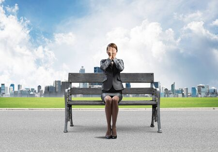 Young woman sitting on wooden bench outdoors. Girl in business suit keeps hands on face for surprise. Hide from problems. Help and successful solutions. Modern cityline panorama in sunny day