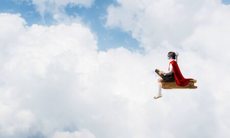 Little child in mask and cape floating on book in sky and reading
