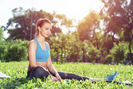Beautiful smiling girl in sportswear relax in park. Young woman with sitting on green grass after training. Meditation outdoor at sunny summer day. Morning exercises and healthy lifestyle.