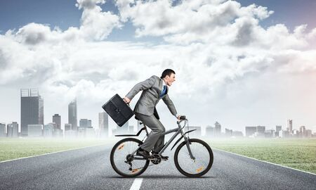 Man wearing business suit riding bicycle outdoor. Young cyclist with suitcase on background of city panorama and blue sky. Time management and business activity. Businessman hurrying to work