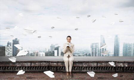 Elegant woman playing trumpet on edge of roof. Girl in white business suit and gloves posing on roof of building. Flying paper planes in blue sky. Blue sky and modern metropolis with skyscrapers.