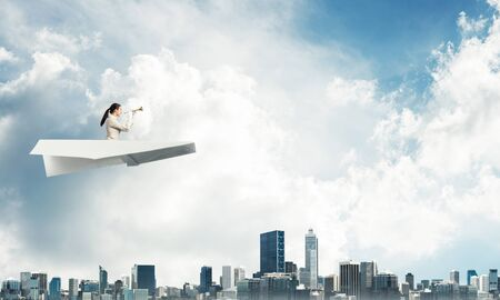 Business woman playing trumpet brass in blue sky. Young lady in white business suit and gloves flying in paper plane with music instrument. Business assistance and support concept with musician.
