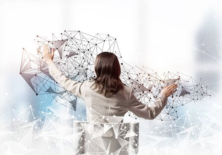 Businesswoman finger pointing on abstract network structure. Back view long haired woman in white suit sitting on white chair. Social connection and networking. Global cloud technology concept