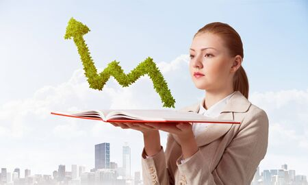Businesswoman with green plant shaped growing arrow graph above opened notebook. Business statistics and analytics. Elegant young woman in white business suit on background of cityscape and blue sky.
