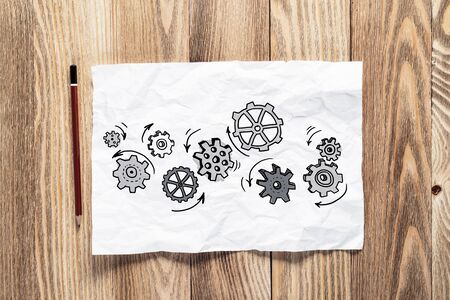 Rotating gears pencil hand drawn. Mechanical technology and machine engineering symbol. Engine mechanism with cogwheels sketch on wooden surface. Workplace with paper and pencil on wooden desk.