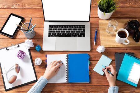 Business woman writing in notebook at office desk. Online business learning and education. Flat lay office workplace with female hands, laptop and documents. Digital technology and coworking space