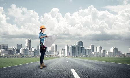 Young woman in safety helmet standing on asphalt highway with blueprint. Architect in workwear checking work progress on background of cityscape. Road infrastructure reconstruction and development.