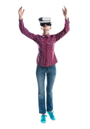 Young woman wearing virtual reality glasses against gray background. Beautiful woman in checkered shirt and jeans with hands up. Interacting with digital interface. Future technology concept Фото со стока