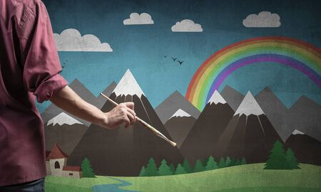 Close up artist hand holding paintbrush. Painter in shirt standing on background colorful picture. Summer landscape with mountains, blue sky and rainbow artwork. Creative hobby and profession. Фото со стока