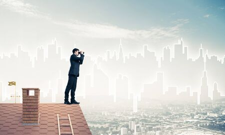 Young businessman viewing cityscape in his binoculars Mixed media Foto de archivo